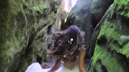 hippi : Cute bride in a wedding dress runs between the rocks, and looks at the camera with a great smile. Happy faces, emotions Stok Video