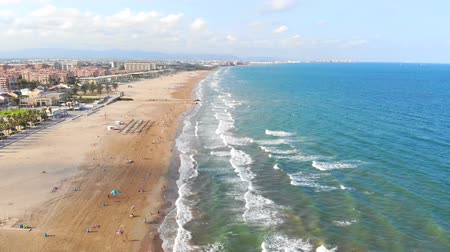 солнечные ванны : Aerial view over the beach in Valencia, Spain. Flight drones over the beach in Valencia. View of the tourist city Стоковые видеозаписи