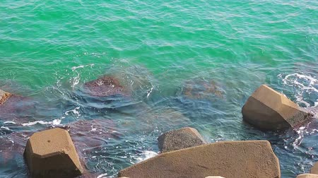 mole : Small sea waves hit the stone that protects the pier. Protection of the pier from the great waves. Stock Footage