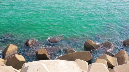 golfbreker : Small sea waves hit the stone that protects the pier. Protection of the pier from the great waves. Stockvideo