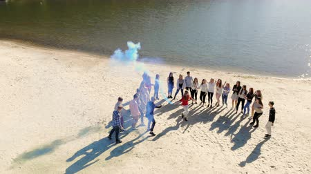 friendship dance : Aerial view group people dance and relax on the shore of the lake. Colored smoke from the firewalls around them. The concept of happy people
