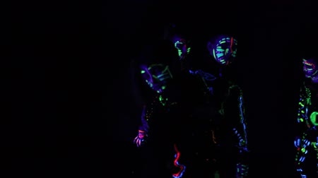 ballroom : creative group of children in colorful costumes that glow in the dark, creates abstract movements. The costumes that glow in the dark room are painted in paints