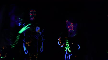 papucs : group of children performs performances in a dark hall, in colorful costumes. Paint in costumes shines in the dark. Choreographic setting of a group of children