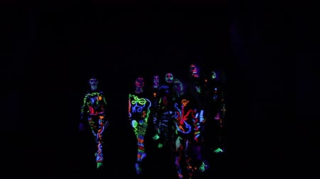 ayak parmakları : group of children performs performances in a dark hall, in colorful costumes. Paint in costumes shines in the dark. Choreographic setting of a group of children