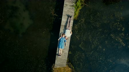 hayran olmak : Aerial view on top. Two lovers of young people lie on a wooden bridge. Fairy tale around a young couple. Happy young couple. Stok Video