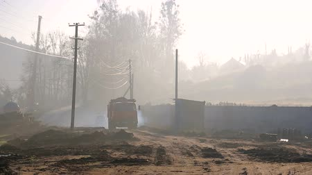 растворение : The truck moves along the construction site. Morning fog and smoke around.