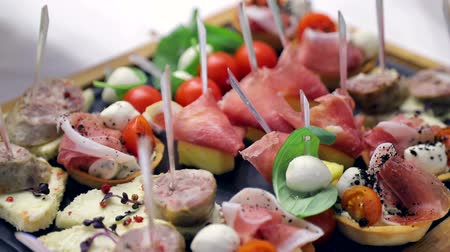 shish : Close up buffet table. Sandwiches with sausage, tomato and mozzarella. Delicious snacks on the Banquet table Stock Footage
