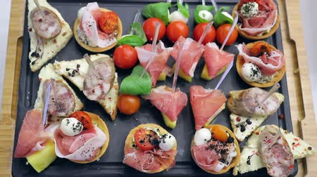 brusinka : Background of the banquet table. Sandwich canapes on the buffet table. Red tomatoes with mozzarella cheese with herbs and sausage with bread Dostupné videozáznamy