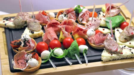 ham : Sandwich canapes on the buffet table. Red tomatoes with mozzarella cheese with herbs and sausage with bread