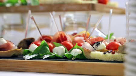 dried tomatoes : Close up buffet table. Sandwiches with sausage, tomato and mozzarella. Delicious snacks on the Banquet table Stock Footage