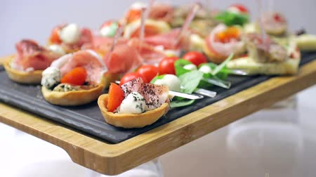 kızılcık : Close up sandwich canapes on the buffet table. Red tomatoes with mozzarella cheese with herbs and sausage with bread Stok Video