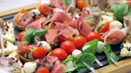 brusinka : Sandwich canapes on the buffet table. Red tomatoes with mozzarella cheese with herbs and sausage with bread