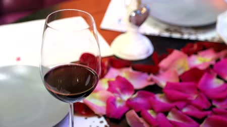 каберне : A glass of red wine standing on the table covered with petals of roses