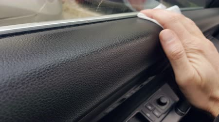 detailing : The mans hand cleans the cars car from the dust using a damp cloth. Car cleaning