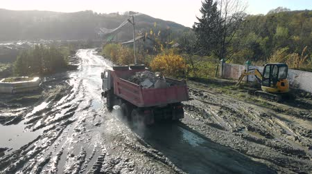taş ocağı : A truck of kamaz loaded with construction debris goes to the swamp. Construction site after rain.