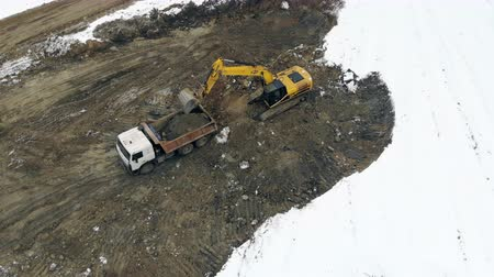 caminhão : UKRAINE LVIV December 29th 2018. Aerial view excavator loads the truck with the ground. Clearing the construction site. Swamp on the construction site