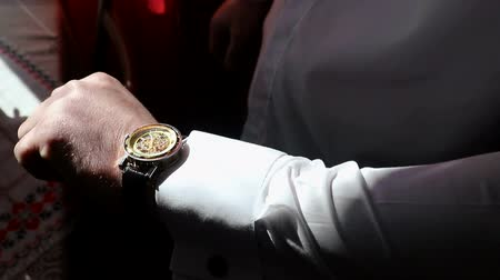 ponctualité : A young business man wears an expensive golden watch on his arm. Looking at the clock and hiding his hand.