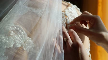 evli : Womens hands close-up button buttons on a wedding dress. A wedding day, the rays of the sun fall on the brides back