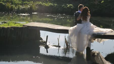 evli : The brides sit on a wooden bridge near the river. Happy family couple, spending time in the park Stok Video