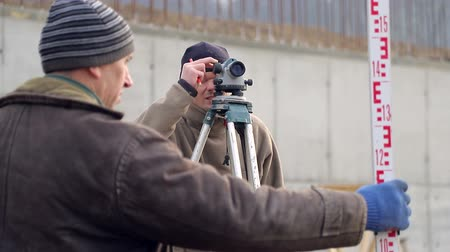 inspecting : Builders using the construction level of the level, carry out measurements Stock Footage