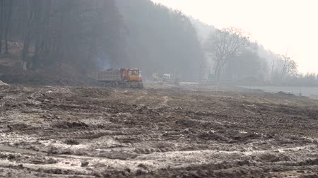 earthworks : Bulldozer machine is leveling construction site. Work of large equipment at the construction site Stock Footage