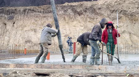 スラブ : Pouring concrete mix from cement mixer on concreting formwork. A group of workers pouring concrete on a construction site