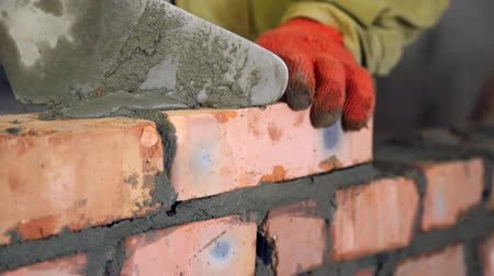 кирпичная кладка : Bricklaying. Hands that put a brick on a construction site