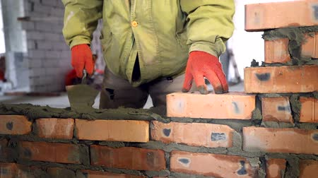 kőműves : Bricklaying. Hands that put a brick on a construction site
