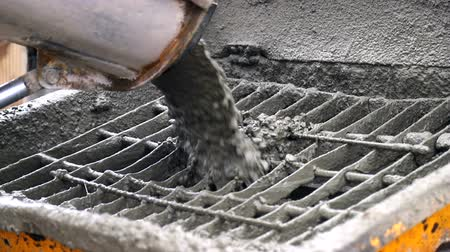 hormigonera : Concrete from the concrete mixer gets into the concrete feeder. Close-up of concrete particles moving slowly