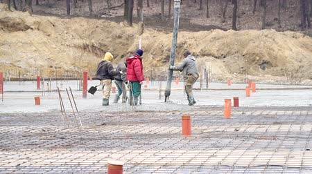 reinforced concrete : Pouring concrete mix from cement mixer on concreting formwork. A group of workers pouring concrete on a construction site