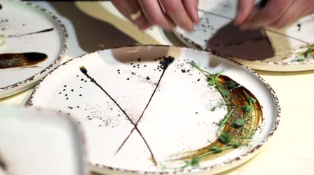 служить : Rui cooks decorate a plate with herbs