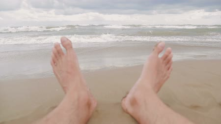 human foot : Close-up of mens feet on the beach. A look at the sea waves that come to the shore. Summer vacation holiday. Stock Footage