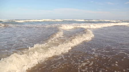 изумруд : Movement of the camera over the waves. Wave comes close to the shore, the sun shines in the water. The sea wave is washed by the picturesque shore of white sand. Background or texture