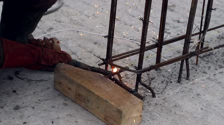 arco : An employee welds a metal structure on a construction site. Construction works. Work outdoor
