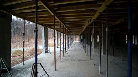 plafond : Movement of the camera between the building supports that support concrete structures. Unfinished floor on the construction site