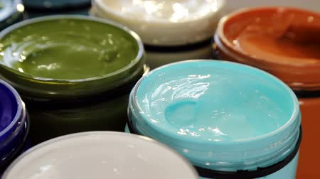 guache : Preparing to draw. Close - up of large cans of acrylic paint of different colors that stand on the table in a composition with flowers. Stock Footage