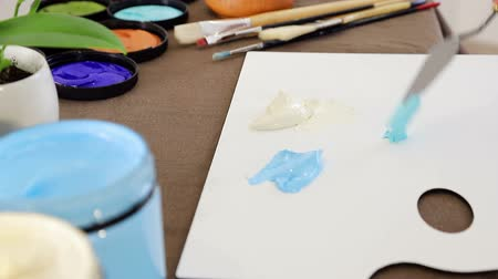 obra prima : Artist puts a blue paint spatula on the palette to mix colors.