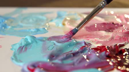 boya fırçası : Artist mixes different colors of acrylic paint with a brush for drawing. Preparation of colors for drawing pictures Stok Video