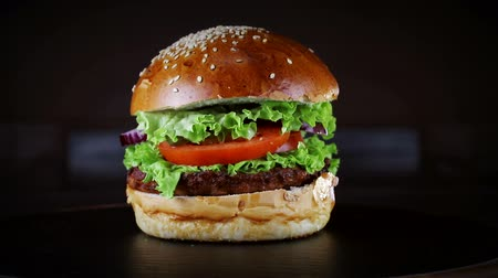 mustár : Burger with cutlet rotates on a wooden Board on a black background.