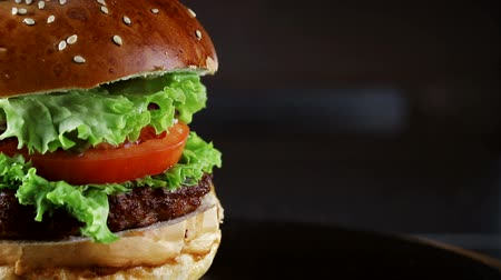 кунжут : Burger, with a cutlet of tomatoes and herbs, rotates on a wooden Board. From the black background. Стоковые видеозаписи