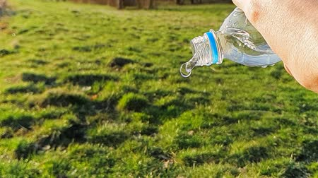 üdítő : Close-up of water flowing out of a plastic bottle, on a background of green grass. 1000FPS slow motion