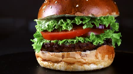 mustár : Burger close-up on a black background. Greens, tomato, and chicken as the ingredients of the Burger. Fast food