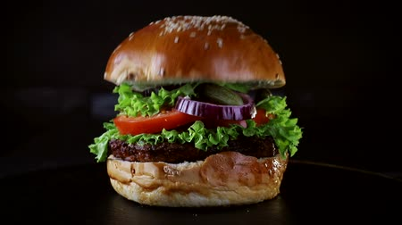 кунжут : The bun falls on the Burger in slow motion. Fast food. Delicious Burger on black background Стоковые видеозаписи