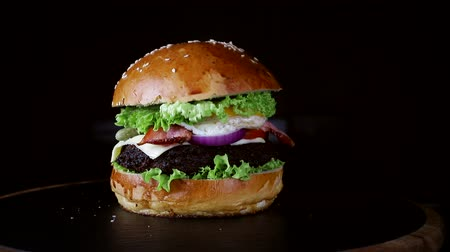 sezam : The bun falls on the Burger in slow motion. Fast food. Delicious Burger on black background Wideo