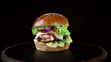 hardal : Fast food. Burger with baked chops, greens, tomato and onions, slowly spinning on a wooden Board on a black background Stok Video