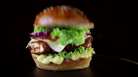 american cuisine : The bun falls on the Burger in slow motion. Fast food. Delicious Burger on black background Stock Footage