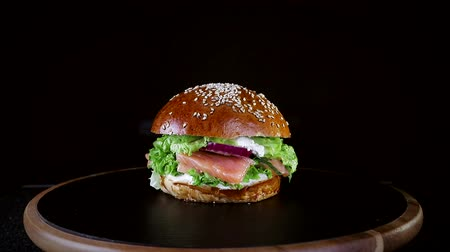 mosterd : Fast food. Burger with red fish, salmon and trout greens, tomato and onion, slowly spinning on a wooden Board on a black background