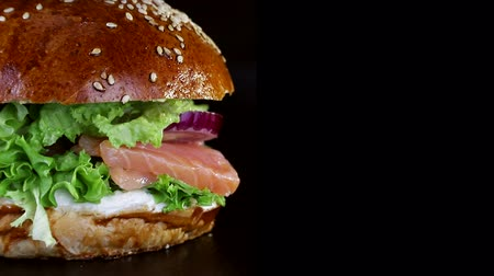 american cuisine : Fast food. Burger with red fish, salmon and trout greens, tomato and onion, slowly spinning on a wooden Board on a black background