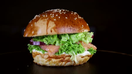 mustár : The bun falls on the Burger in slow motion. Fast food. Delicious Burger on black background Stock mozgókép