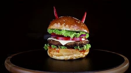 mustár : Fast food. Burger with red pepper, slowly spinning on a wooden Board on a black background Stock mozgókép